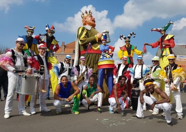 spectacle deambulatoire coloré avec acrobate musiciens et echassier
