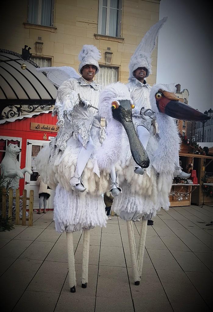 spectacle de rue avec echassiers oiseaux blanc