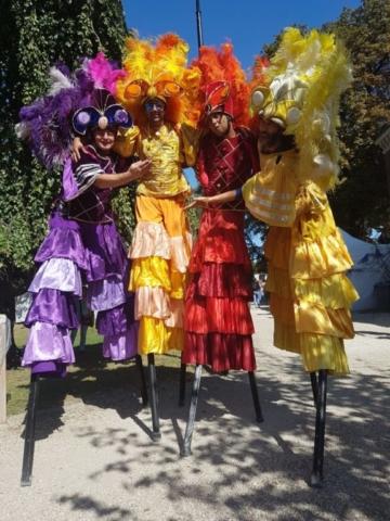 spectacle de rue avec echassiers danseurs samba